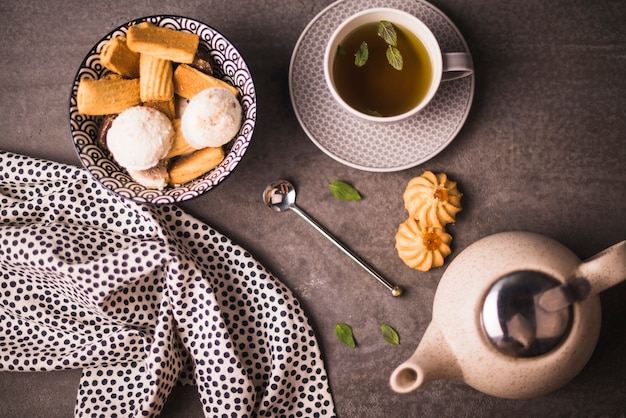 Cookies and herbal tea near polka dotted textile on rough surface