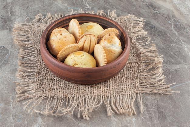 Печенье в миске на текстуре заделывают на мраморе.