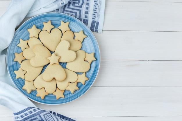 나무와 부엌 수건 배경에 접시에 쿠키. 평면도.