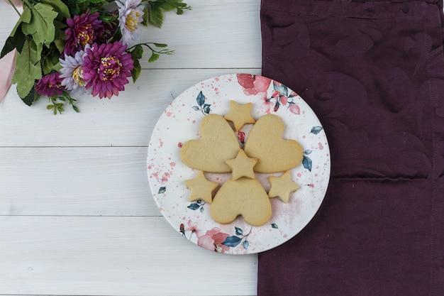 평평한 꽃과 함께 접시에 쿠키는 나무와 섬유 배경에 누워