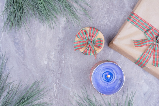 Печенье в упаковке с голубой горящей свечой и подарочной коробкой вокруг.