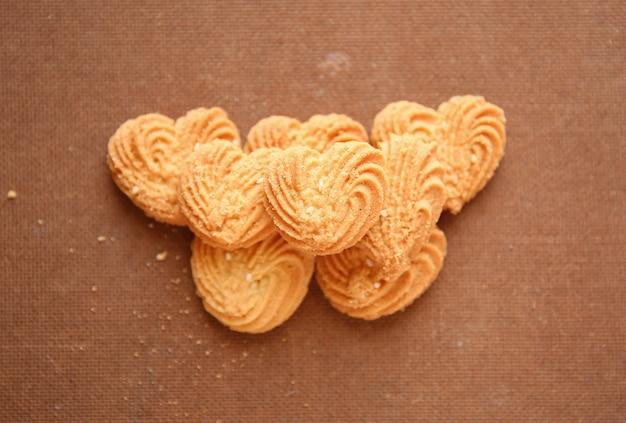 나무 배경에 나무 바구니가 달린 하트 모양의 쿠키