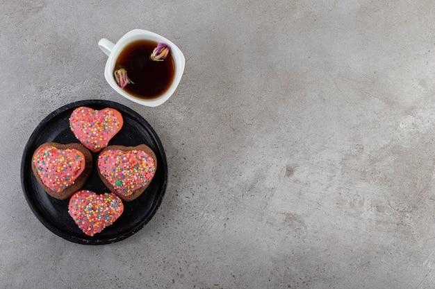 뿌려진 하트 모양의 쿠키와 돌 테이블 위에 놓인 차 한잔.