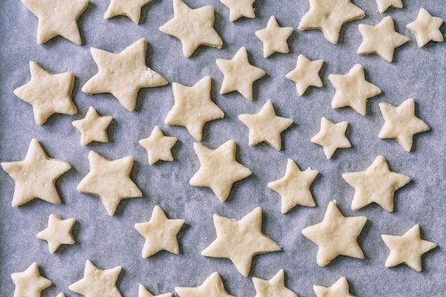 パーチメント紙の星の形のクッキーは、ベーキングトレイにあります