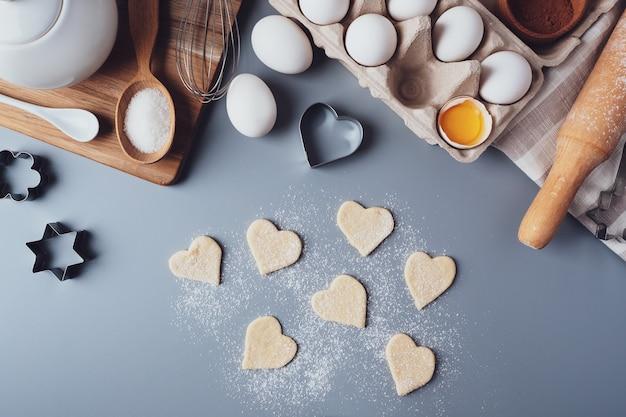 ハートの形をしたクッキー。灰色の背景に自家製クッキーを作るための材料。バレンタインデー、父の日、母の日のお菓子を作るというコンセプト。フラットレイ、上面図。