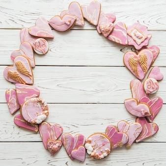 Печенье в форме мраморных сердечек на белом деревянном фоне, сложенное по кругу, копией пространства