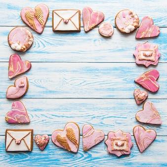 Печенье в форме мраморных сердечек на белом деревянном фоне, сложенное в квадрат, копия пространства