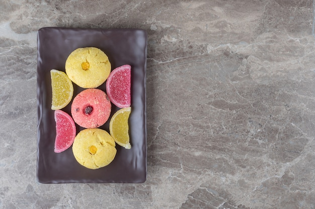 Biscotti e caramelle gommose impacchettate su un vassoio su una superficie di marmo