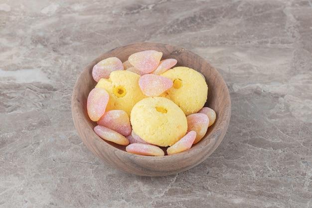 Biscotti e caramelle gommose impacchettate in una piccola ciotola su una superficie di marmo