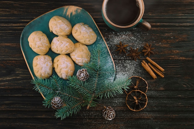 Cookies like cones on a birch-tree plate with spruce sprig and cup of coffee on a wooden table.