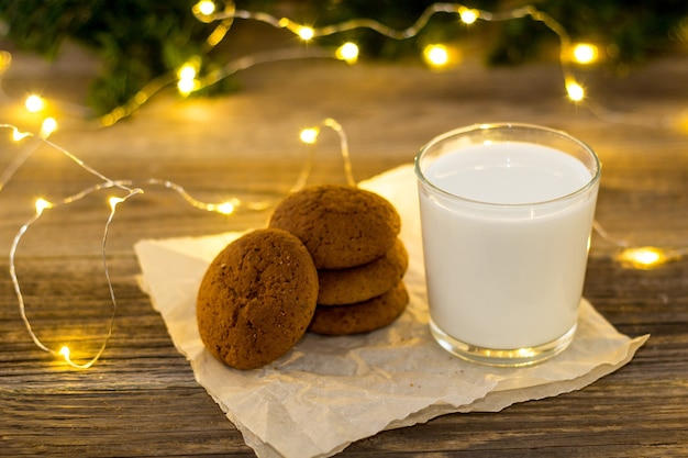 Cookies and milk in glass for santa claus in front of a christmas light bokeh. new year concept