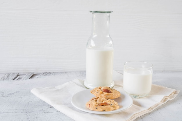 Cookies and milk on white wooden background
