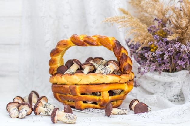 Cookies mushrooms glazed in white and brown chocolate in wicker basket of dough. dessert. beautiful sweet
