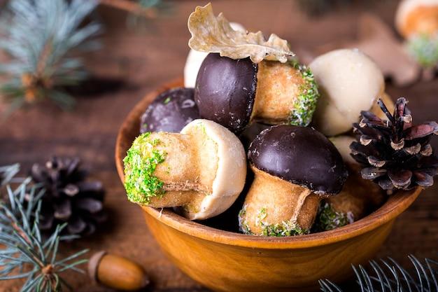 木製の背景に木製のボウルにクッキーキノコ