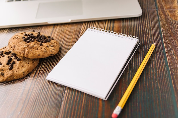 Cookies near notebook with pencil and laptop