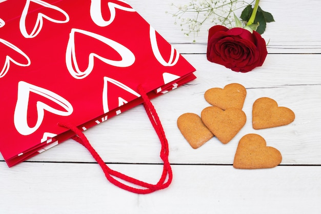 Cookies near present bag and flower