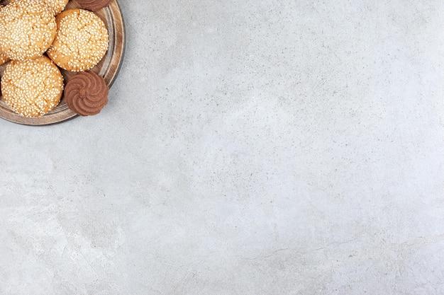 Печенье аккуратно уложено на деревянной доске на мраморном фоне. фото высокого качества