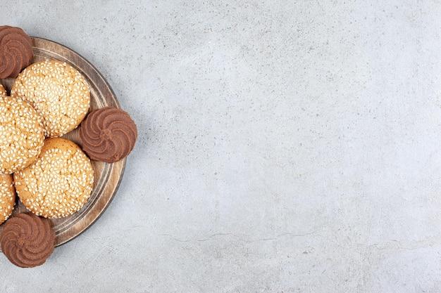 大理石の背景の木の板にきちんと積み上げられたクッキー。
