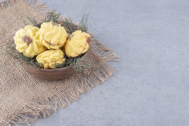 大理石のテーブルの松の葉のボウルに入れ子になったクッキー。