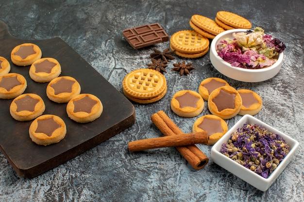 Печенье o деревянное блюдо с палочками корицы и сухими цветами на сером