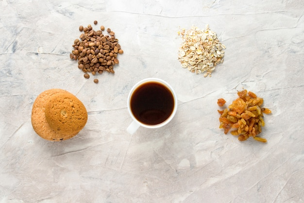 Cookies, oatmeal, coffee, raisins and a cup of coffee on a light background. breakfast concept
