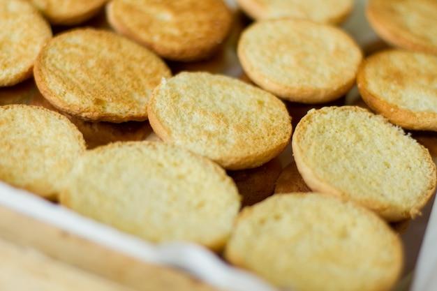 黄色のクッキー。丸い形のビスケット。自宅で甘いおやつを用意します。キッチンの焼きたてのペストリー。