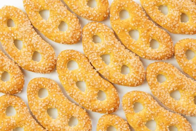 Печенье желтого цвета, сладкие крендели в сахаре, крупные кристаллы сахара, на белом фоне, изолированные
