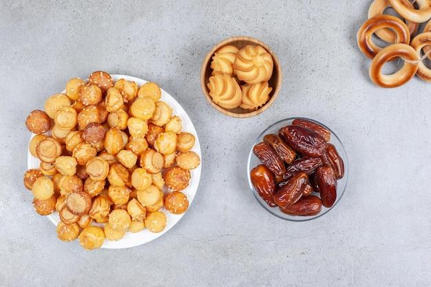 접시와 그릇에 담긴 쿠키와 약간의 묶인 sushki 옆에있는 그릇과 대리석 표면에 소수의 날짜