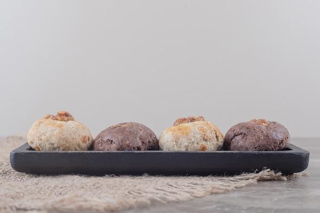 大理石の布の上の小さなトレイ上のクッキー