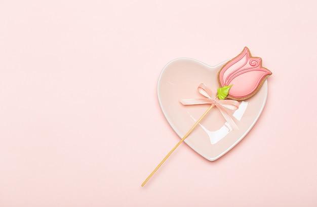 Печенье на палочке-тюльпан на розовой тарелке в форме сердца на розовом фоне