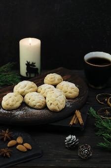 Печенье на деревянной доске, чашка кофе и свеча