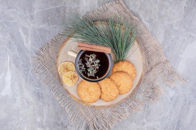 Печенье на деревянной доске с чашкой чая вокруг.