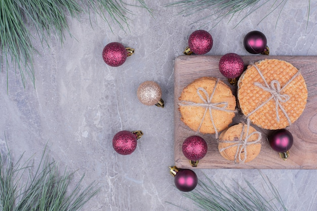 Печенье на деревянной доске с красными блестками елочные шары вокруг