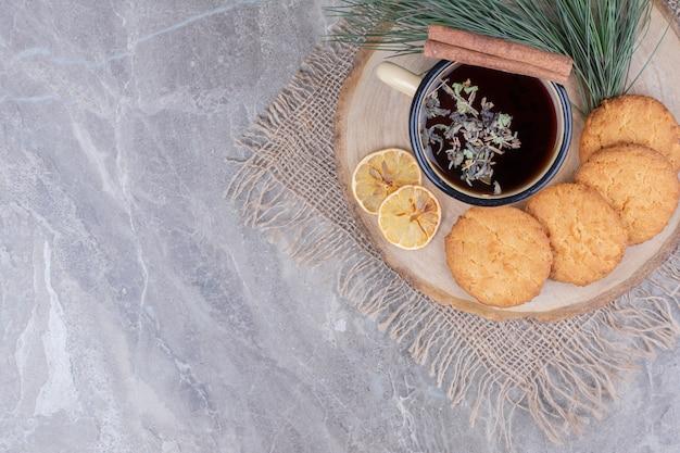 Печенье на деревянном блюде с чашкой глиняного вина и ломтиками лимона вокруг