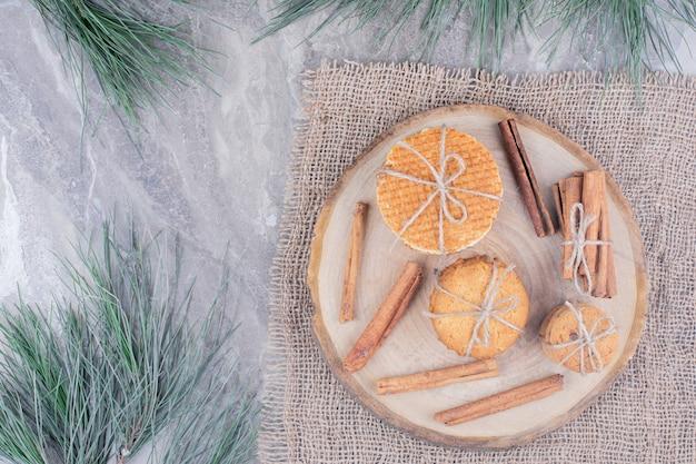 Печенье на деревянном блюде с палочками корицы вокруг