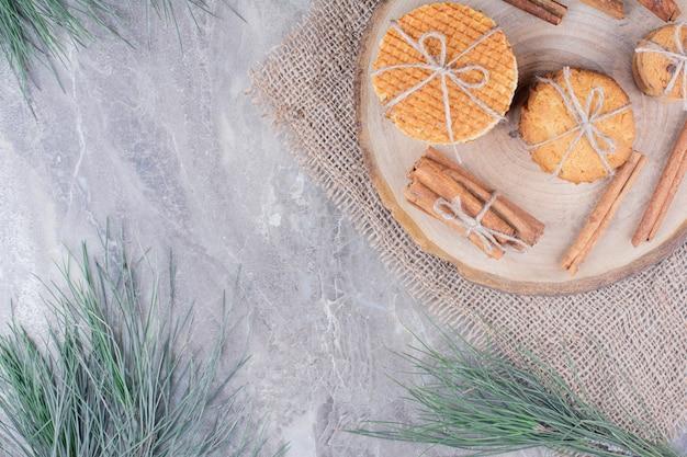 シナモンスティックが周りにある木製の大皿のクッキー