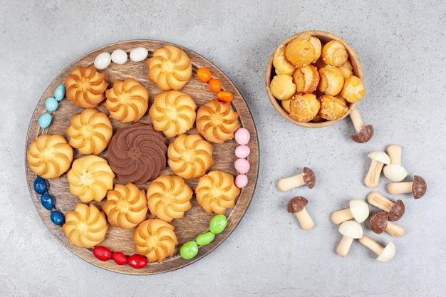 Печенье на деревянном подносе, окруженном конфетами, и в миске с рассыпанной связкой шоколадных грибов на мраморном фоне. фото высокого качества