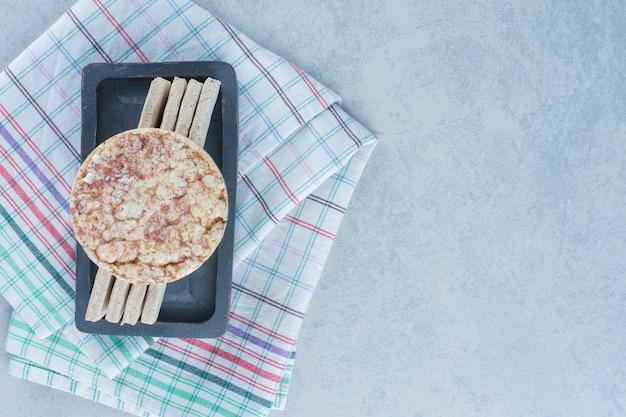 大理石のタオルの上にトレイに並べて積み上げられたクラッカーのクッキー。
