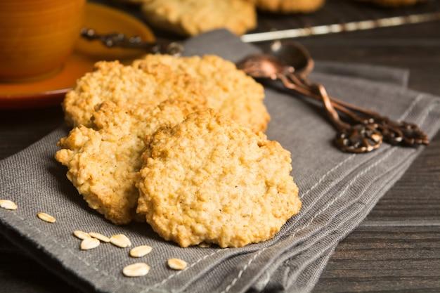Печенье на серой ткани с завтраком с чаем или кофе, домашнее овсяное печенье