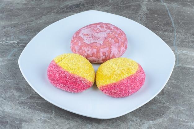복숭아 형태의 쿠키와 하얀 접시에 있는 분홍색 쿠키. 사진을 닫습니다.