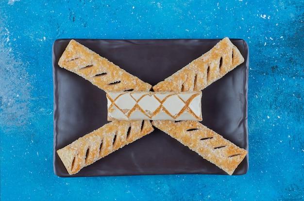 Печенье на деревянном подносе, на синем фоне. фото высокого качества
