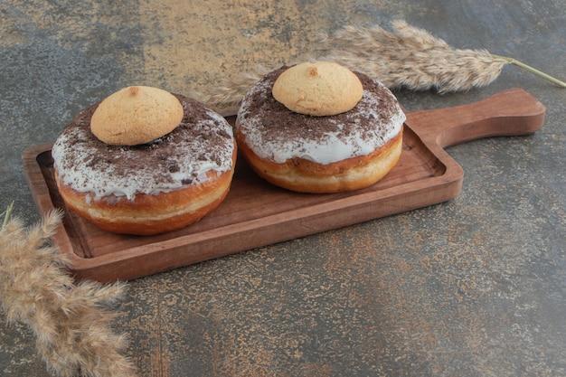 木製のテーブルの上の木の板のドーナツの上にクッキー