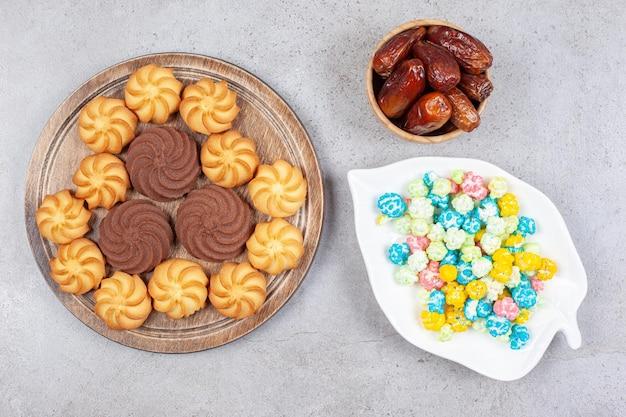 Печенье на деревянной доске рядом с тарелкой конфет и миской фиников на мраморном фоне. фото высокого качества