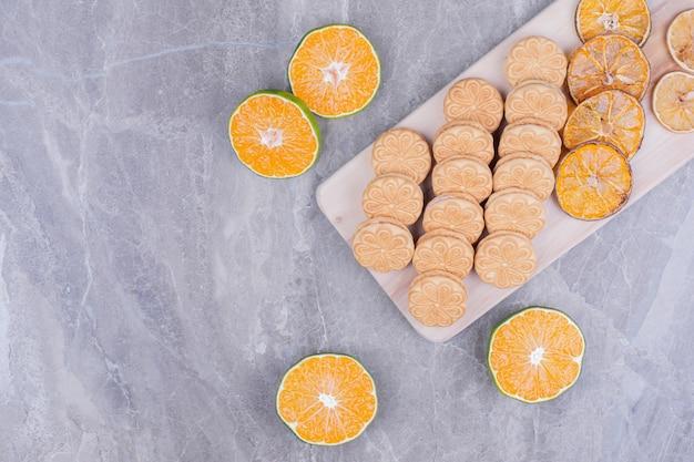 Печенье на деревянной доске с дольками апельсина вокруг.