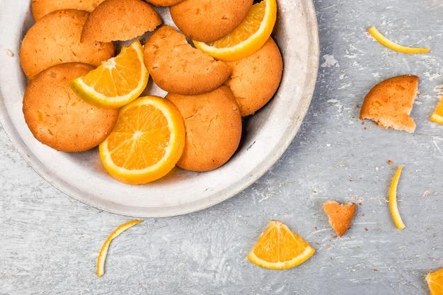 Cookies and orange citrus fruit on metal plate on grey . flat lay