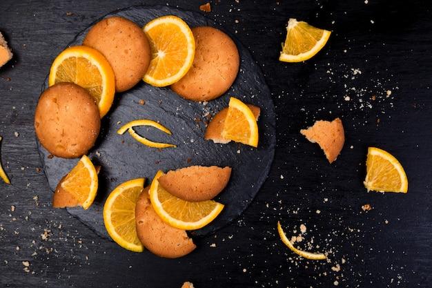 Cookies and orange citrus fruit on slate plate on black surface,