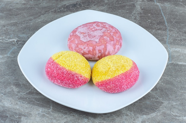 Biscotti a forma di pesca e biscotto rosa sul piatto bianco. foto ravvicinata.