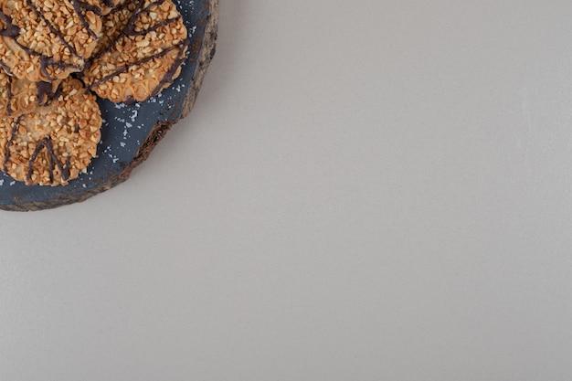 大理石の背景の木の板に積み上げられたクッキー。