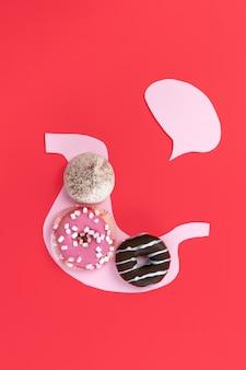 Biscotti sullo stomaco rosa. concetto di nutrizione malsana. composizione concettuale con copyspace sul rosso