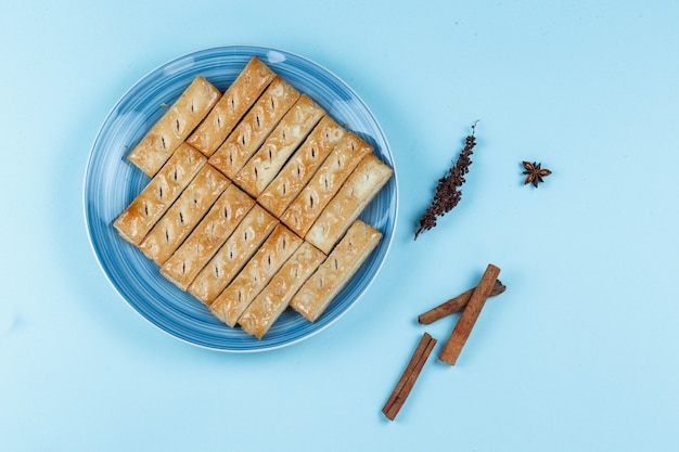 Cookies on a plate with dried herbs and spices on blue background